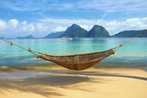 A hammock at the beach with the view of Bacuit Archipelago islands - El Nido, Philippines