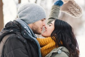 A happy young man and woman kissing in winter enjoying life and